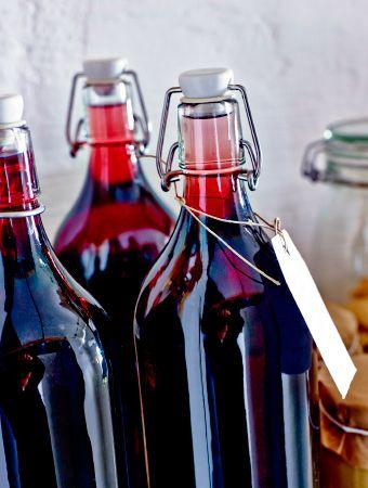 Nærbilde av tre IKEA-glassflasker med rød fruktdrikk.