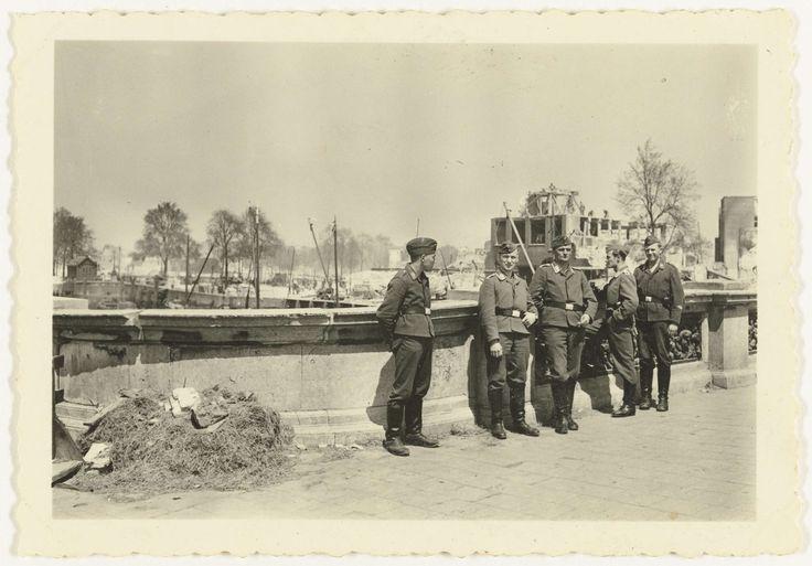 Anonymous | Duitse soldaten bij verwoeste huizen, Anonymous, 1940 | Vijf Duitse soldaten poseren bij een brug met op de achtergrond de verwoeste huizen in Rotterdam.