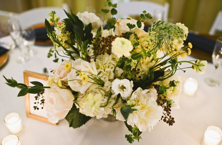 large arrangement of white hydrangea, yellow stock, anemone, privet berry, queen anne's lace, star of Bethlehem, bupleurum,yellow button chamomile, pale yellow ranunculus, Amelia roses & white lisianthus in low footed mercury glass