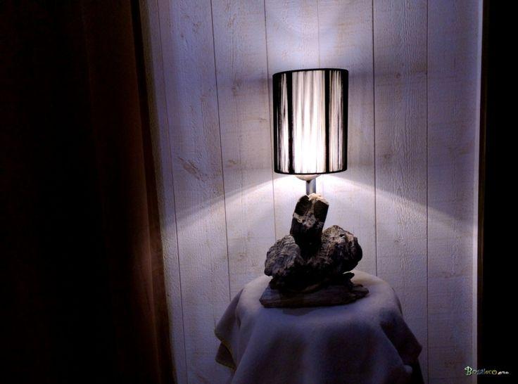 Lampe de taille moyenne en bois flotté de ton gris clair. Elle est coiffée d'un abat-jour noir à fils.  Bois : Bois flotté récolté sur les plages du Finistère sud. Le bois a été nettoyé et assemblé. Aucun traitement.  Pied métalique : Tube en acier brossé.  Eclairage : Diffusion sous abat-jour. Créé avec une ampoule LED 12 volts 36 LEDs à 360 degrés. Consommation: 6.5W rendu : 45W  Abat-jour : Cylindrique noir à fils.