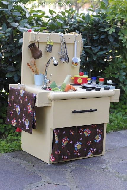 Cucina giocattolo da un comodino.  Qualche mese fà, io e Sbubbu abbiamo realizzato la cucina per il Picci. Abbiamo usato un comodino preso al mercatino dell'usato, ci abbiamo attaccato una tavola di legno dietro e lo abbiamo verniciato. Abbiamo fatto un buco per il lavandino (ho comprato una ciotola per cani ), due cd dipinti per i fornelli, un rubinetto a poco prezzo (3,50euro), tre tappi di sughero come pomelli per accendere il gas e due mensole per le spezie che già avevamo.