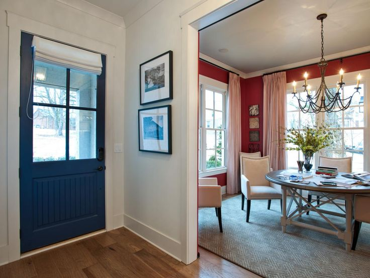 A navy blue front door makes a colorful welcome in this home's foyer, especially when paired with the red walls of the adjacent dining room. A Roman shade lets down over the door's windows for more privacy.