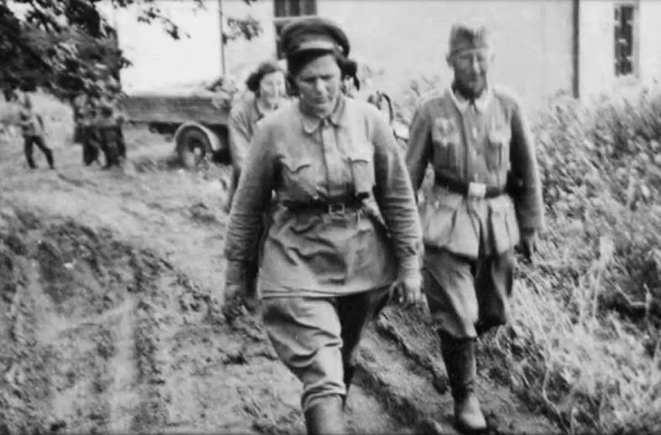 POW Russian woman officer is taken to interrogation. Women POWs were usually shot before moving any larger POW groups to confinement.