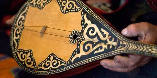 An instrument of China's nomads, the Dömbra: The long-necked fretted two-stringed lute of the Kazakhs. This slender cedar wood instrument is associated with Kazakhs' nomadic heritage, and is an essential part of their tradition of oral history.