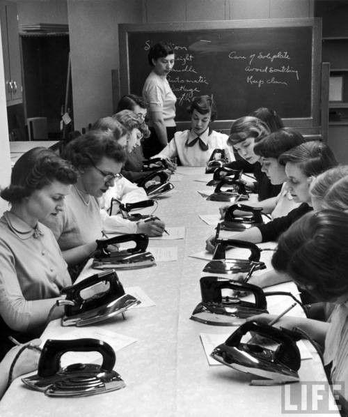Meisjes op de huishoudschool leren strijken.
