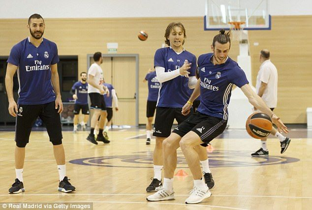 Luka Modric (centre) attempts to take the ball off Bale at Real Madrid's basketball arena
