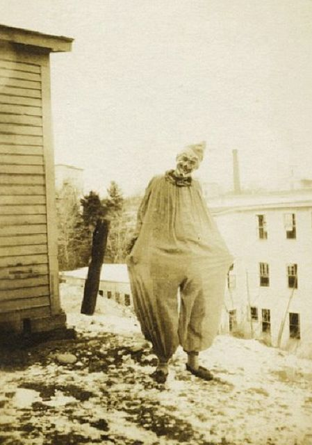 The Clown    This is a creepy old photograph of someone dressed up as a clown and lurking around a lonesome corner on a winter day. There is nothing to identify this man or to indicate exactly when or where this photograph was taken.