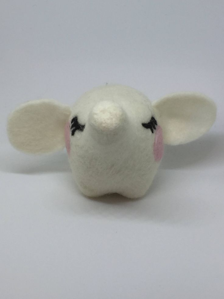 This peaceful dreamy elephant is crafted from needle felted merino wool. It has a lovely rounded body, blushing cheeks and beautiful eyelashes!  The elephant stands at approximately 10cm tall.