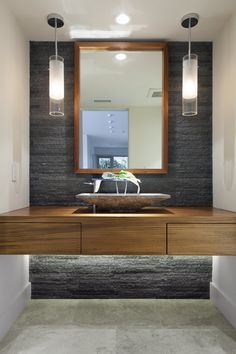 A modern bathroom with natural stone accent wall and pendant lights.