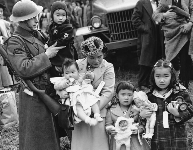 <p>Mrs. Shigeho Kitamoto had no time for tears when she was evacuated along with other Japanese from Bainbridge Island in Washington State, March 30, 1942. She has too busy looking after her four children. Corporal George Bushy, member of the military guard which supervised the departure of 237 Japanese for California, gave her a hand with the youngest. (AP Photo) </p>