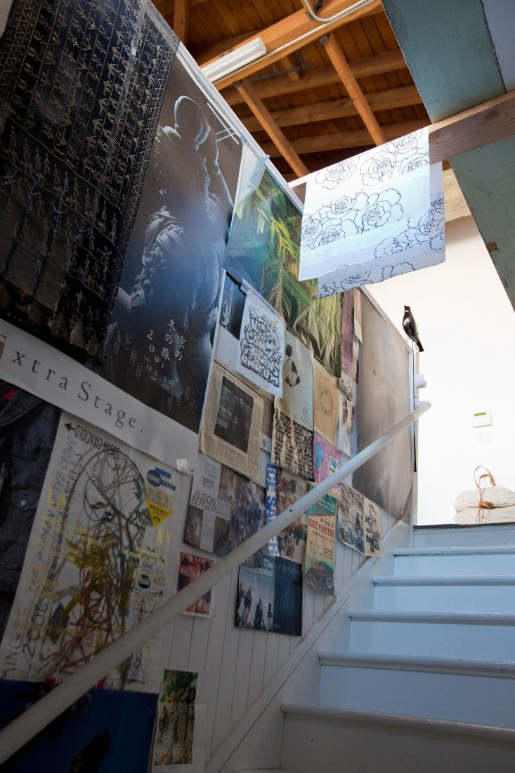 small trade company entry - stair wall layered with posters, magazine pages, newspaper clippings, customer letters...
