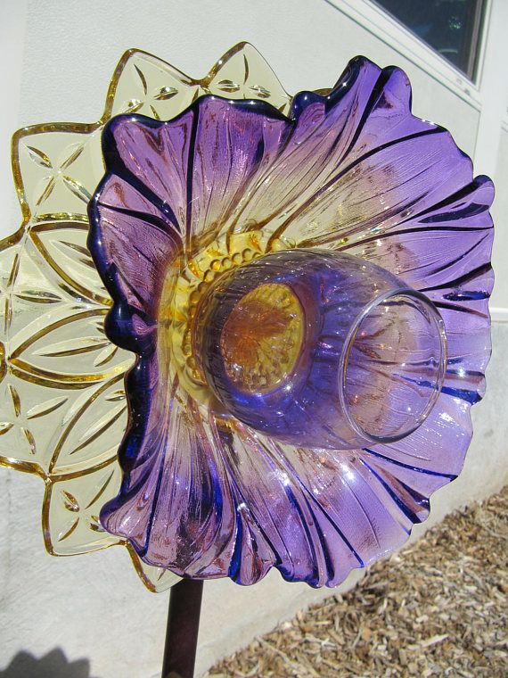 This exquisite vintage glass plate flower is simply striking! It is made only of high quality collectable vintage glass. It has not been painted. It is approx. 9  inches in width. It has been created to be staked outdoors in the garden. It can also be enjoyed indoors, sitting on a plate stand near a sunny window. I have  used three pieces of glass in this piece. In the rear of the flower, I have included a Federal Glass yellow plate, It is vintage from the 1960s. The bowl in the  center is a…