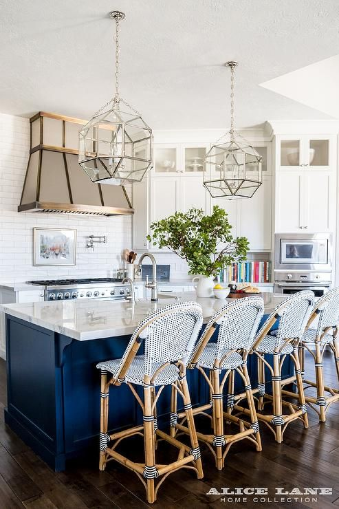 A kitchen island painted in Benjamin Moore Hale Navy is fitted with a white macaubas quartzite countertop seating Serena