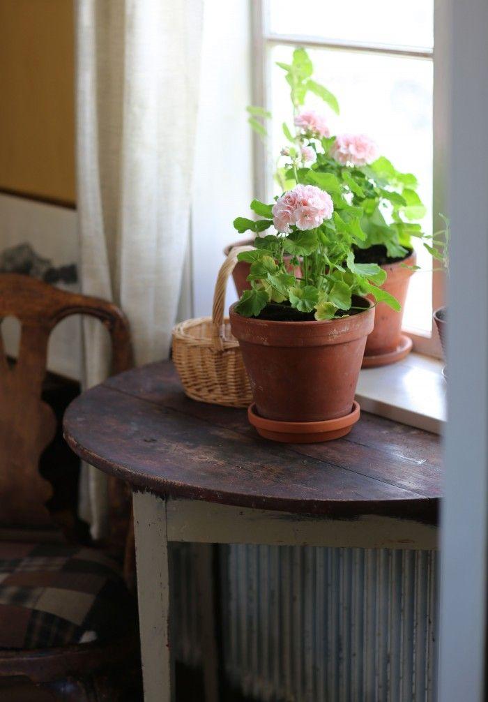 Halvcirkelbord vid fönstret ger plats för mer blommor.