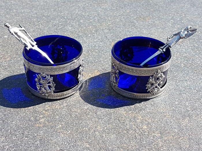 """Mooie paar zout kelders sterling zilver en kobalt blauw glas  Mooie paar van zout kelders in STERLING zilver met kobalt blauwe glas voeringen.Minerva van hoofd hallmark 1e leerjaar. Uit de 20e eeuw.STERLING zilver Minerva van hoofd 1e rang hallmark (950 / 1000).De zilversmid hallmark """"A-G"""" met een engel ANGELO Guy 1912.Veel omvat ook twee kleine antieke lepels voor zout en peper met het holle gedeelte van de lepels zoals gevormde Jakobsvrucht schelpen. Mantel-vormige lepels.(waarschijnlijk…"""