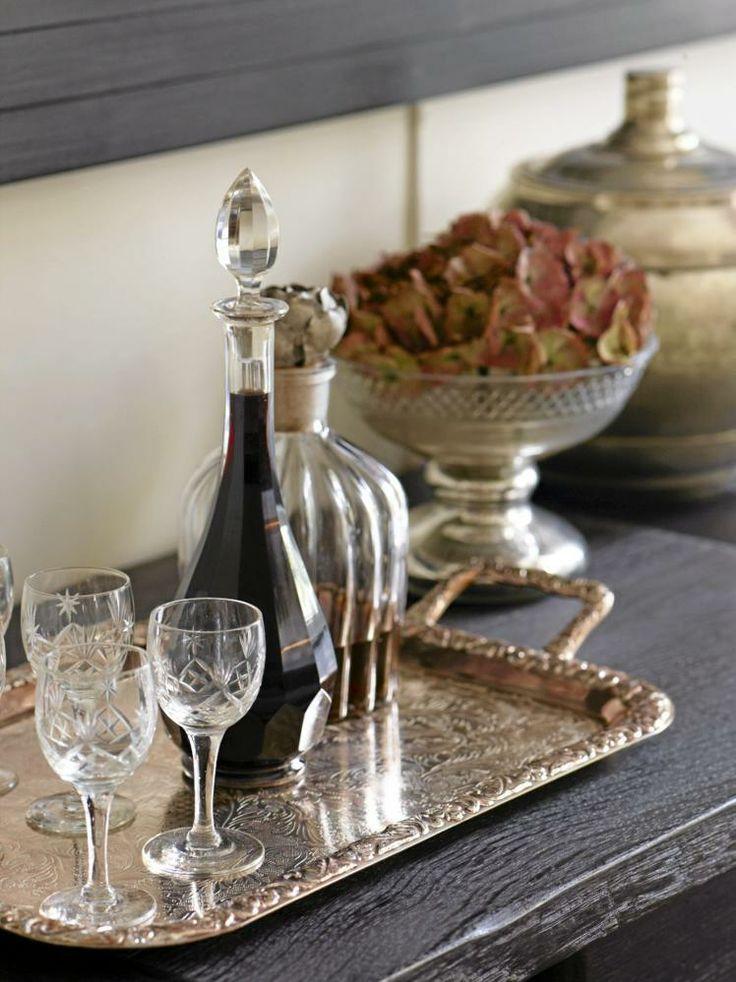 Krystallglass, karafler og et sølvbrett er arvet, og plassert på et gammelt konsollbord sammen med reisefunn fra Afrika.