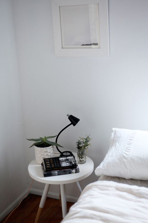 """Sneak Peek: Claire Cottrell. """"White dipped wood table picked up on sale at West Elm. Vintage black Underwriters' Laboratories portable lamp with peach cord from Duson in Silver Lake. A plant and a stack of current before-bed reads."""" #sneakpeek"""