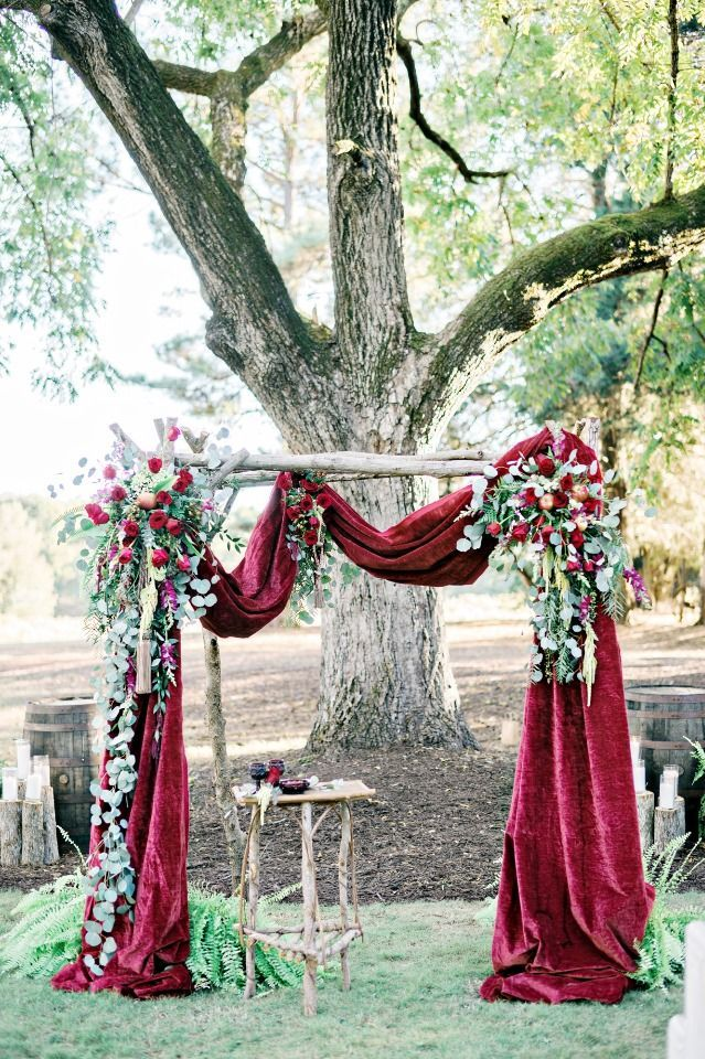 deep red velvet draped wedding arch