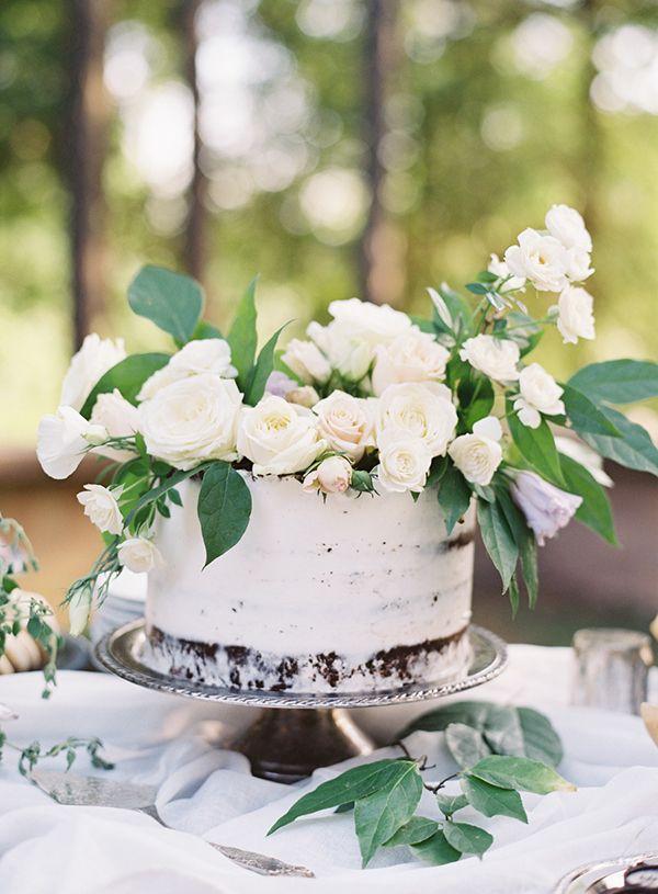 Witte bruidstaart overladen met prachtige verse witte bloemen en groene bladeren