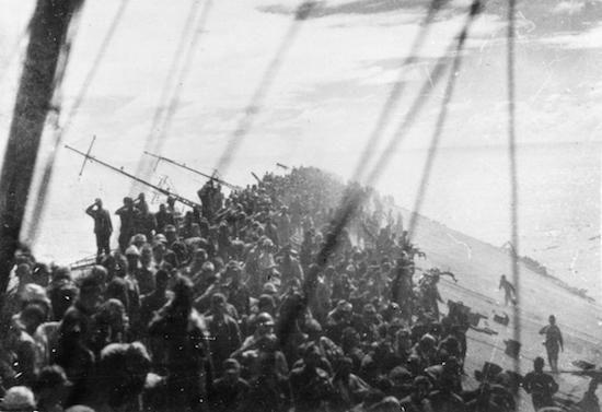 Soldados dan un último saludo a la bandera Japonesa, mientras su buque de guerra se hunde.