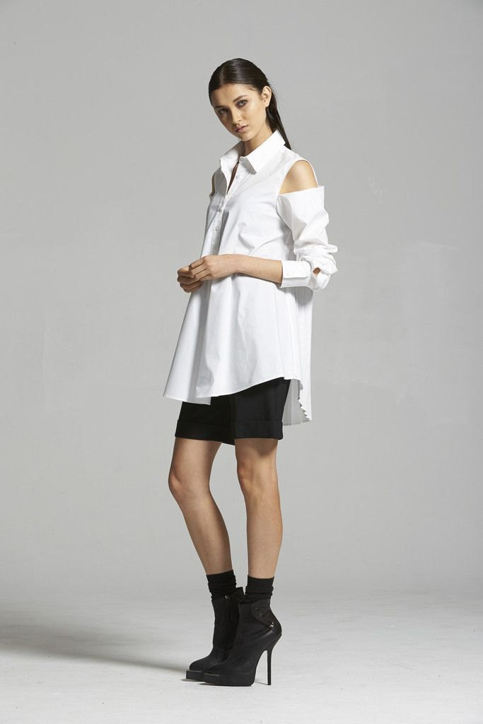 Trapeze Shirt - White Our Trapeze Shirt is a modern, sharp, tailored shirt with a twist. The pleated back section and deconstructed shoulder detail make this shirt a real statement without compromising on functionality or comfort. The pleated section of the shirt creates a beautiful silhouette from the back whilst adding texture and interest. Wear the sleeves unbuttoned at the shoulder for an edgy look or button up for a work appropriate shirt with a cool edge