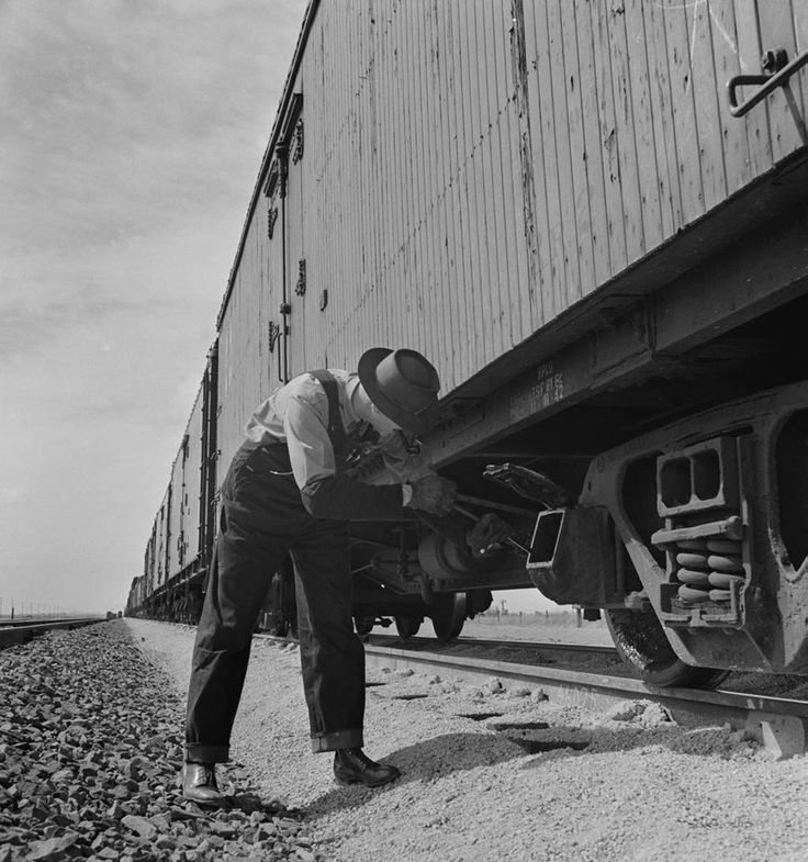 """Santa Fe conductor E.K. Hill inspects the journal (repacking?) of a reefer on a siding near Texico, New Mexico during March of 1943. The oil-soaked materials used to lubricate the bearings, such as rags, wool, or cotton, would occasionally overheat which led to the notorious """"hot box."""" Jack Delano photo."""