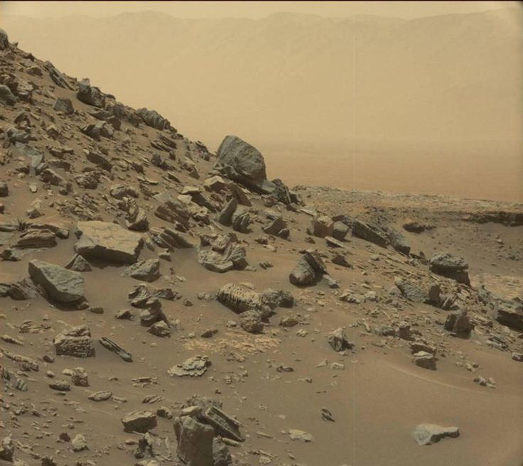 """15 New Incredible Photos from NASA's Archives - The rim of Gale Crater is visible in the distance, through the dusty haze, in this view of NASA's Curiosity rover of a sloping hillside on Mount Sharp within the """"Murray Buttes"""" region of Mars, on Sept. 8, 2016. This photo was taken during the 1454th Martian day, or sol, of Curiosity's work on Mars; NASA dispatched the rover in 2012."""