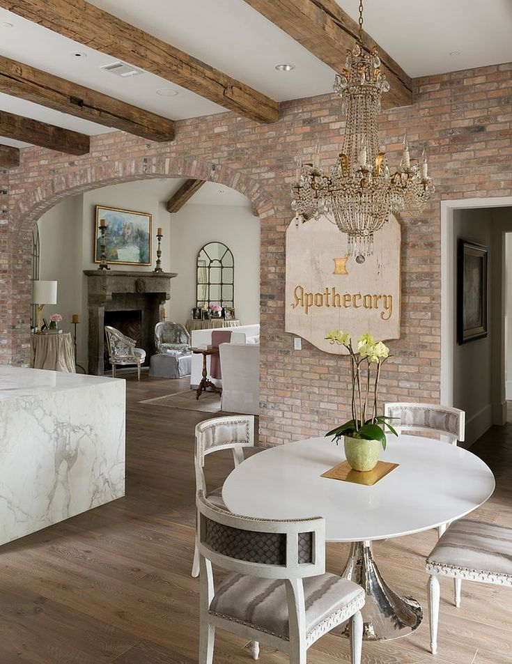 A Chic Midcentury Modern Dining Table Is Unexpectedly Paired With An Ornate  Chandelier In This Beautiful Dining Space. Exposed Brick Walls And Wood  Ceiling ...