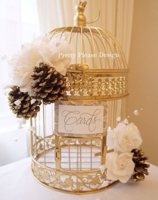 """Pretty in glitter tipped pinecones is this chic gold birdcage prettified with lace, hand calligraphy that reads """"Cards"""", ivory blooms + delicate touches of pearls. The perfect accessory to compliment a Christmas/Winter Wonderland wedding."""
