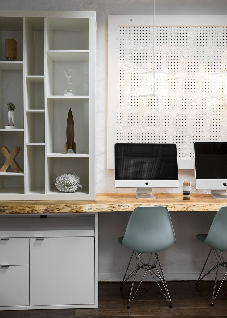 The wooden desktop plays off the other, freestanding desk, but is topped with computers, plenty of shelving, and peg board. The blue Eames side chairs add a infusion of color to the work space.