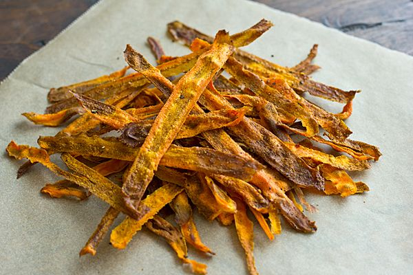 curried baked carrot chips  1 large carrot, peeled  1 tsp. olive oil  1/2 to 1 tsp. sweet curry powder (stick with 1/2 teaspoon for milder chips)  salt + pepper to taste