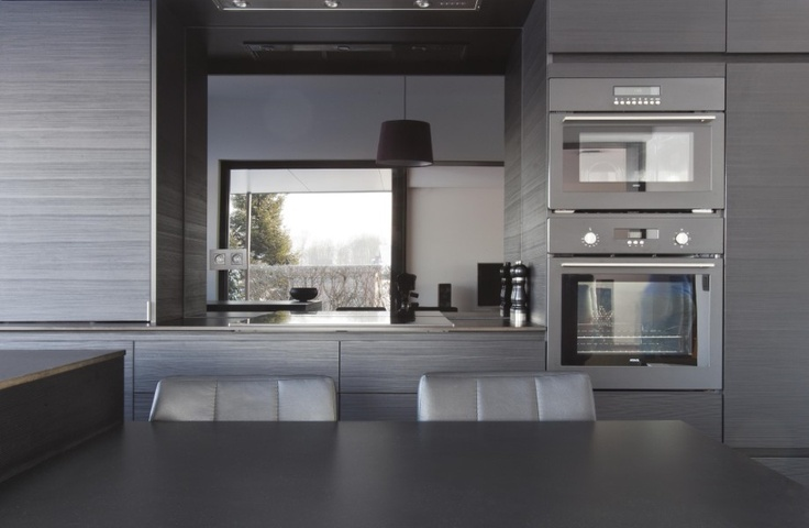 Een zwarte keuken met zwarte stoelen en een zwarte leistenen vloer, DMOA Architecten
