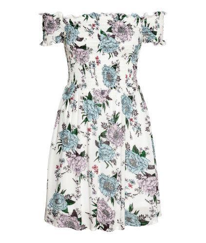 Vit/Blommig. En kort klänning i krinklad, vävd viskos. Klänningen har bara axlar med smock upptill och kort ärm. Avskuren i midjan med lätt utställd kjol.