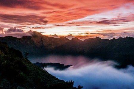 Eg Giwangkara S: Mount Rinjani or Gunung Rinjani is an active volcano in Indonesia on the island of Lombok. Administratively the mountain is in the Regency of North Lombok, West Nusa Tenggara (Indonesian: Nusa Tenggara Barat, NTB). It rises to 3,726 metres (12,224 ft), making it the second highest volcano in Indonesia  On the top of the volcano is a 6-by-8.5-kilometre (3.7 by 5.3 mi) caldera, which is filled partially by the crater lake known as Segara Anak or Anak Laut (Child of the Sea)…