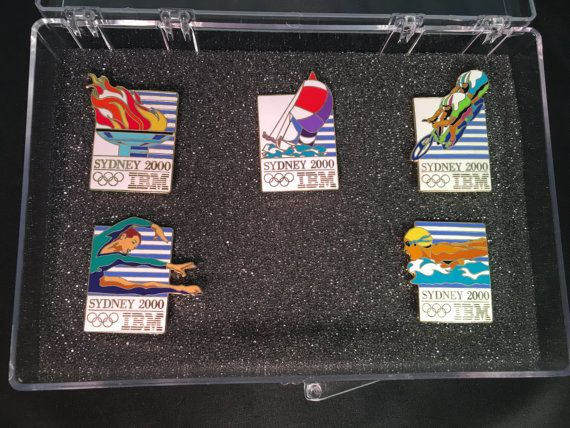IBM 2000 Sydney Olympic Sponsor 5 Pin Badge Collection. Set comes in original plastic case and foam. This set in this casing was only available to employees. Collection of 5 pins from the 2000 Sydney Olympics. Some tough to find pins in this set. Includes torch, sailing, bicycling, gymnastics, and swimming. Please review all photos, and message me if you have any questions