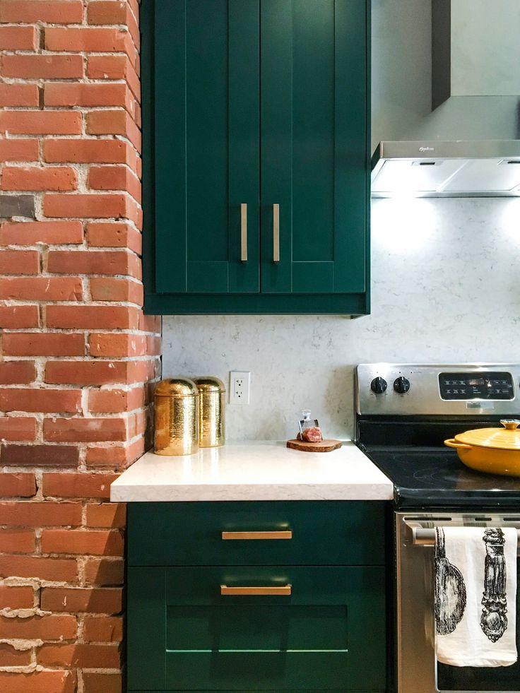 exposed brick, green shaker cabinets, gold hardware, stone backsplash