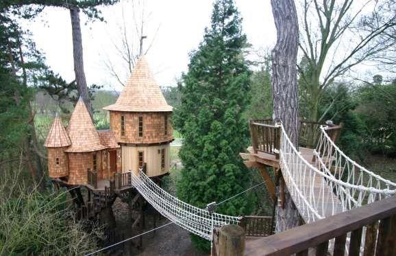 HIGHLIFE TREE HOUSE, HERTFORDSHIRE, INGLATERRA Esta casa na árvore parece saída de um conto de fadas. Ela tem três torres em estilo medieval, conectadas por uma ponte de corda e uma rampa que conduz a uma sala de jogos com vídeogame e TV de plasma.