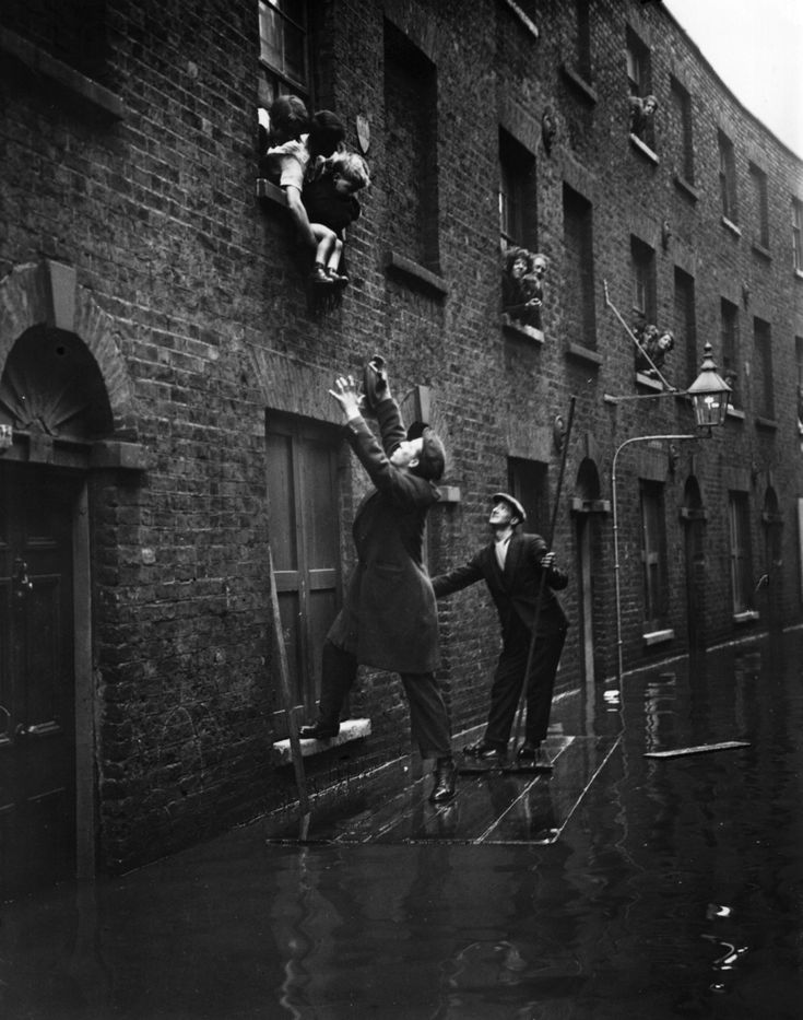 1928: Men rescuing residents in Rotherhithe, south London, from a flood caused by the Thames breaking its banks.