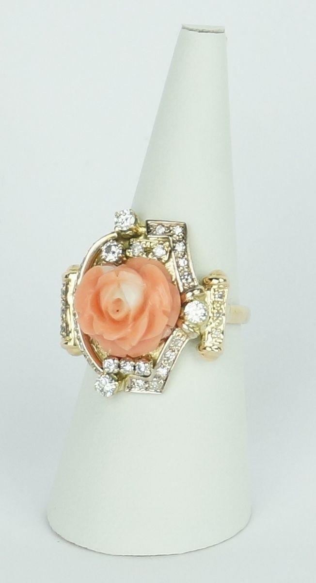 Een 14 krt. bicolore gouden fantasie ring bezet met een gestoken peau d'ange koraal in roosmotief en diverse briljanten