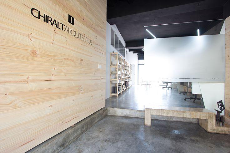 Chiralt Arquitectos I Entrada oficina con mobiliario minimalista e impresionante revestimiento de madera en paredes.