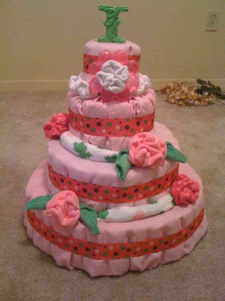 Diaper cake for little girl.  Burp clothes and baby bed blankets cover the layers with wash cloth roses, a teething ring and infant socks on top.