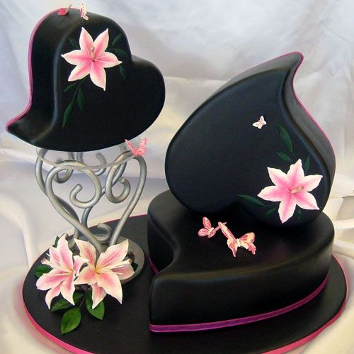 Three heart shaped black wedding cakes, decorated with pink oriental lilies and butterflies.