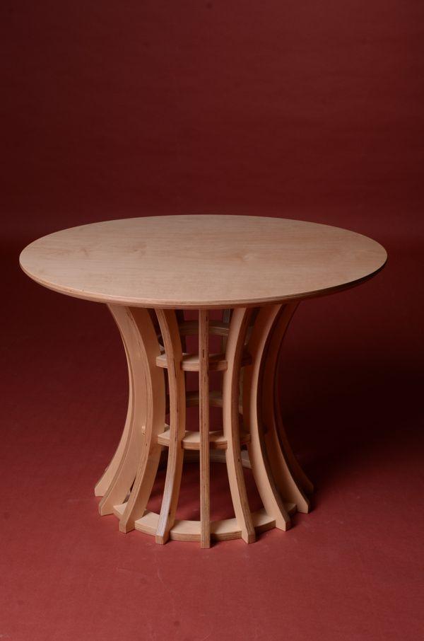 Des lattes arrondies sont assemblées tout autours de pièces circulaire formant ainsi une table avec un pied incurvé.