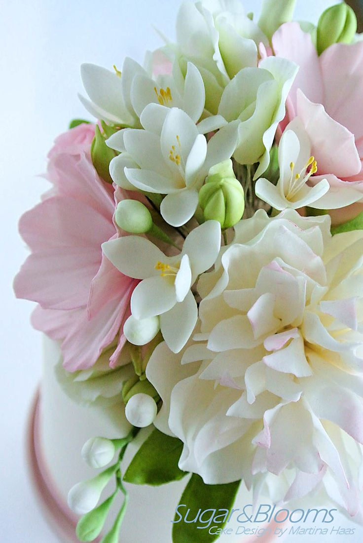 Sugar flower arrangement in white, pink and green shades. Freesias, peony, cosmos, freesias, hydrangeas and english roses are made of sugar paste.