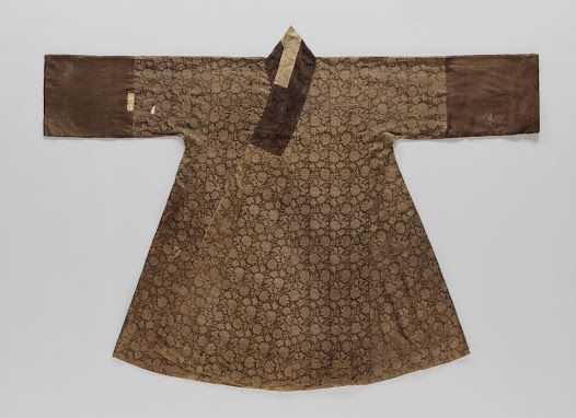 """A Jangot excavated from the romb of Lady Song of Eunjin, the wife of Jung, Eungdoo (丁應斗: 1508∼1572). Jangot was favored as an overcoat for women until late Joseon period. The coat is padded with cotton wool and hand quilted; outer layer is made of silk with a lotus and vine pattern. There are large armhole patches called Moo on each side, they come down along the side seam to help the ease of movement and retain the pleats of the skirt worn inside."" at the Seok Juseon Memorial Museum."