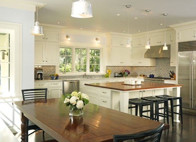 Sunny creamy ivory kitchen design with ivory kitchen cabinets with marble countertops, square kitchen island with butcher block counter tops, black slat counter stools, Jamie Young Lafitte Clear Glass Pendants, gray tiles backsplash, glossy wood farmhouse dining table and black slat dining chairs.