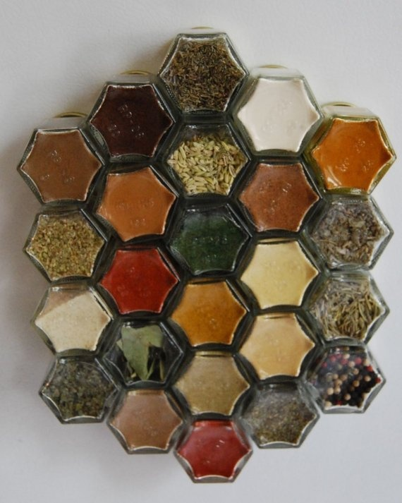 I want a set of these! Set of 24 magnetic spice jars to fit on your fridge. Hexagonal shape fits together creating a spice-colored honeycomb pattern on your fridge. Strong neodymium magnets will keep jars from sliding. Caps are die stamped with spice names.