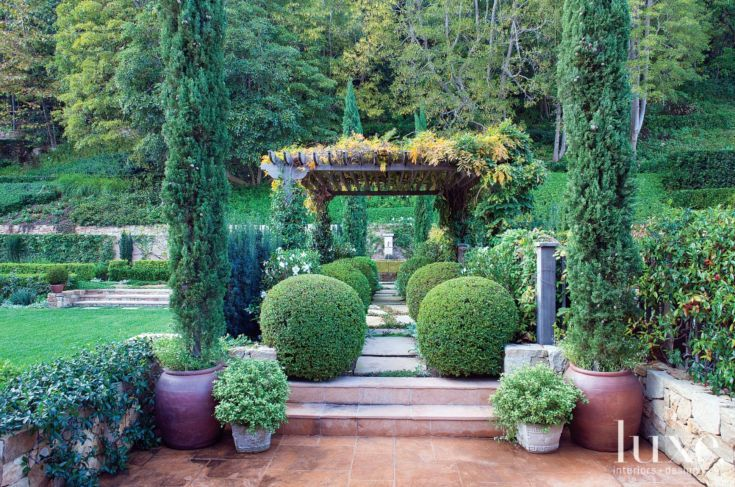 Landscape designer Lisa Zeder created a formal connection between two sections of the backyard using a vine-covered trellis and a pathway lined with symmetrical boxwood globes. The terrace flooring is oakwood flagstone.