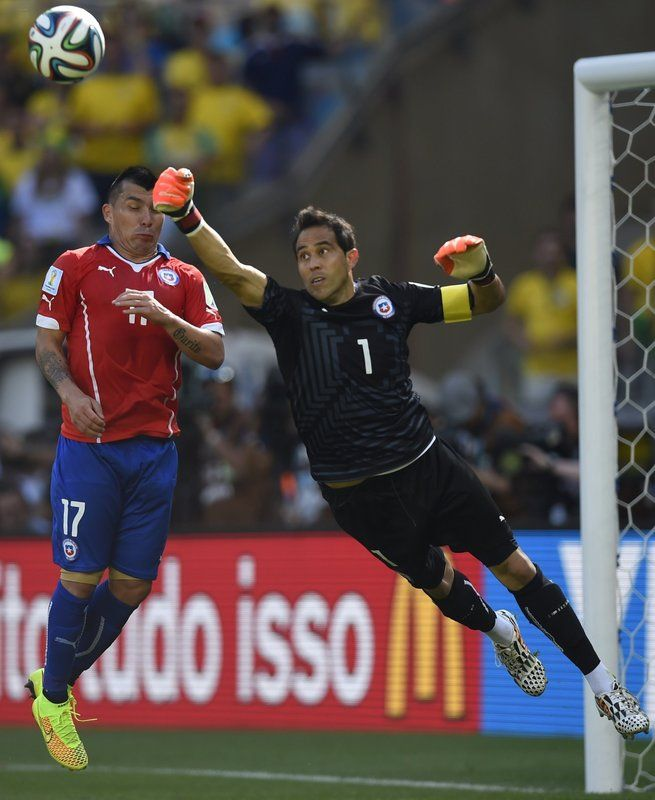 Brasil 1(3) v. Chile 1(2) (6.28.2014) - El Nuevo Herald Chile's goalkeeper and captain Claudio Bravo (R) punches the ball away next to defender Gary Medel during the round of 16 football match between Brazil and Chile at The Mineirao Stadium in Belo Horizonte during the 2014 FIFA World Cup on June 28, 2014. FABRICE COFFRINI / AFP/Getty Images