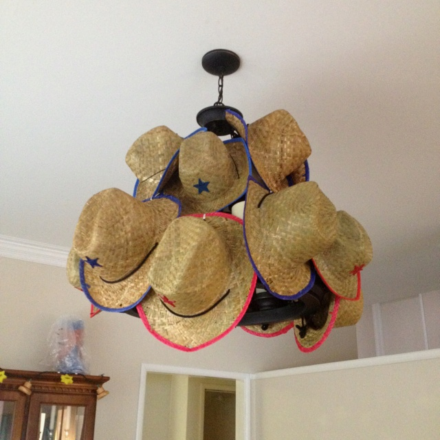 Adult and Children's cowboy hats from Oriental Trading used to make a chandelier for Texas themed party!